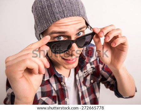 Top view of young man adjusting his sunglasses and looking at camera while standing against grey background. - stock photo
