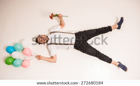Top view of young man is lying on the floor with balloons and flowers. - stock photo