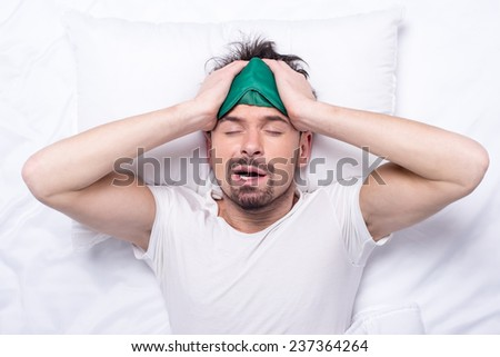 Top view of young sleepy man with sleep mask in the bed. - stock photo