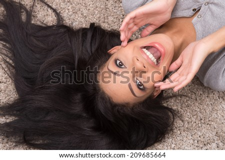 top view of young woman lying on carpet. african girl shouting and holding hands to mouth - stock photo