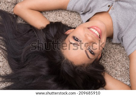 top view of young woman lying on carpet. african girl smiling and looking at ceiling  - stock photo