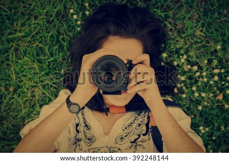 Top view of young woman lying on grass ground with hand holding camera, focus on lens.vintage style filter. - stock photo