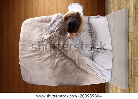 top view of young woman praying in the bedroom - stock photo