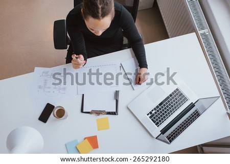 Top view of young woman reviewing chart. Businesswoman analyzing financial data. Female working on company data projections at her desk. - stock photo