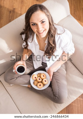 Top view of young woman with a cup of coffee and cookies is looking at the camera. - stock photo