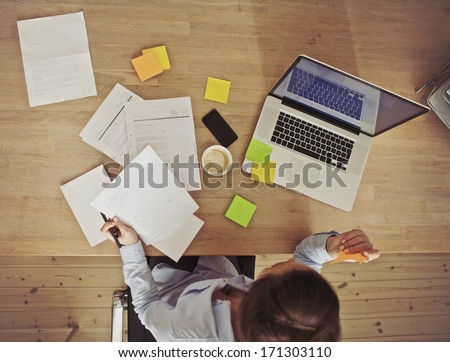 Top view of young woman working at her desk with laptop and documents. Business woman working at desk in office. - stock photo