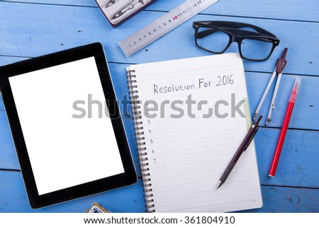 Top view office desk mockup: To do list on black notebooks with pen, blank tablet, eyeglasses, ruler, divider tool on blue wooden background. 2016 new year goals and resolution - stock photo