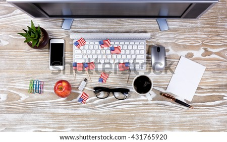 Top View office desktop with USA flags on rustic white wood. Fourth of July holiday concept.