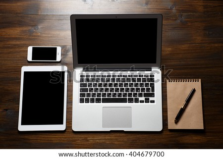 Top view office. laptop, tablet, mobile phone and notepad on wooden table
