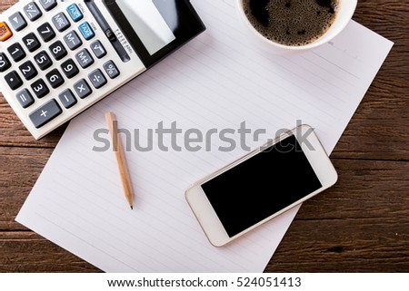 Top view office table with paper and coffee and calculator and black smartphone