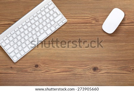 Top view office workplace - keyboard and mouse on dark wooden background with copy space - stock photo