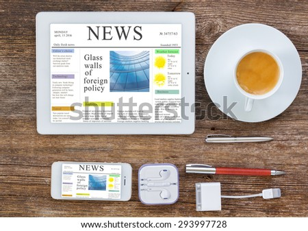 Top view office workplace -  set of tablet, phone and cup of coffee on wooden background, news site on screen - stock photo