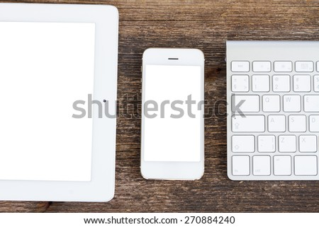 Top view office workplace -  tablet, keyboard and phone on wooden background, copy space on screen  - stock photo