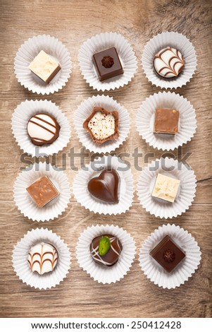 Top view on assorted chocolate pralines on wooden surface - stock photo