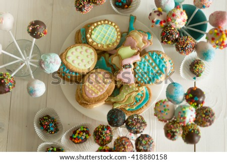Top view on assortment of candies, cake pops and cookies on wooden table at confectionery - stock photo