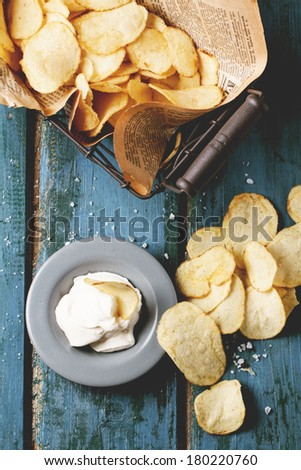 Top view on basket with potato chips with plate of sauce and sea salt over blue wooden table. See series - stock photo