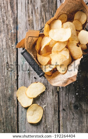 Top view on basket with potato chips with sea salt over old wooden table. See series - stock photo