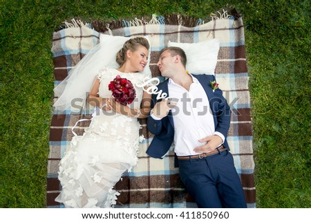 Top view on beautiful happy bride and groom lying on fresh green grass at park - stock photo