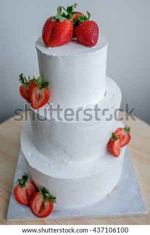 top view on big white cake decorated with red strawberry