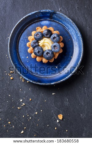 Top view on blueberry mini tart served on blue ceramic plate over dark stone background. - stock photo