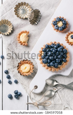 Top view on blueberry mini tarts served on white cutting board with vintage kitchenware. - stock photo
