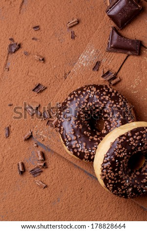 Top view on chocolate donuts and dark chocolate served on cutting board with cocoa powder as background. See series - stock photo