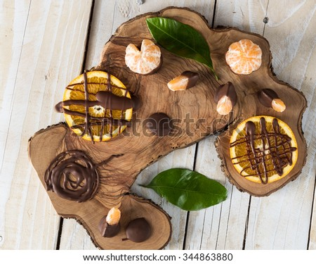 Top view on citruses with chocolate on wooden board - stock photo