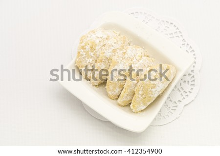Top view on cookies rolled in powdered sugar on white plate and paper doilies. Made of buttery, shortbread style dough with ground nut fillings.   - stock photo