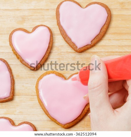 Top view on cookies. Woman ready to write or draw something on a heart shaped cookie.