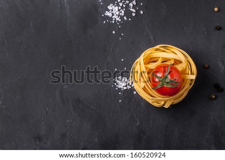 Top view on dry pasta and fresh cherry tomato served with sea salt on dark gray background - stock photo