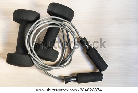 Top view on dumbbells with skipping rope - stock photo