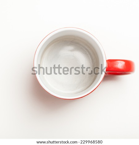 Top view on empty red coffee or tea mug or cup. Studio shot from above on white background. - stock photo