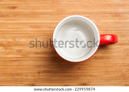 Top view on empty red coffee or tea mug or cup. Studio shot from above on wooden background, underground surface. - stock photo