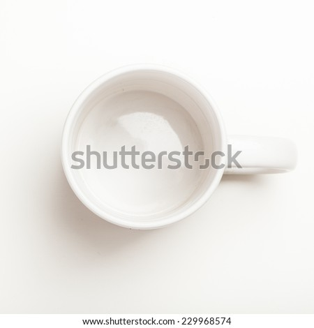 Top view on empty white coffee or tea mug or cup. Studio shot from above on white background.