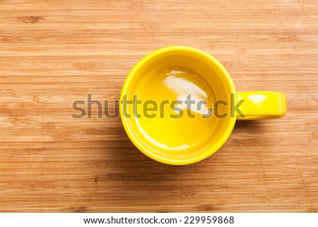 Top view on empty yellow coffee or tea mug or cup. Studio shot from above on wooden background, underground surface. - stock photo