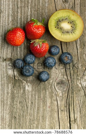 Top view on fresh strawberries, blueberries and kiwi on white table