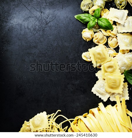 Top view on homemade pasta  with flour and basil on dark vintage background