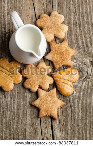 Top view on homemade sugar cookies and jug of milk on old wooden table