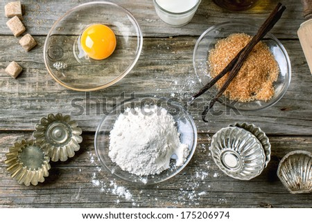 Top view on ingredients for baking (flour, egg, brown sugar, milk) with vintage cupcake's forms on old wooden table. See series - stock photo