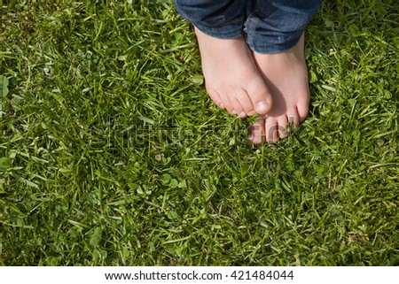Top view on kid's bare feet on the green grass. Little boy standing on the grass in the park on a sunny day. Child's bare feet. - stock photo