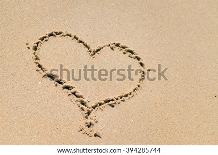 Top view on love heart drawing on the sand. Beach copy space background texture