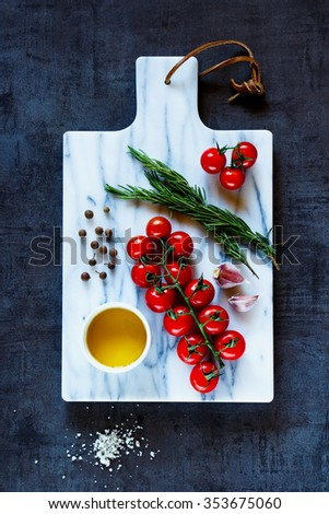 Top view on marble cutting board and healthy ingredients for tasty vegetarian cooking. Diet or vegan food concept.  - stock photo