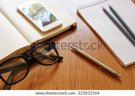 Top view on office workplace with pen in the middle - stock photo