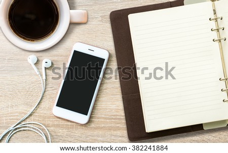 Top view on opened notebook, smartphone, and cup of coffee on dark wooden office desk. - stock photo
