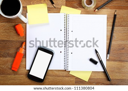 Top view on opened notebook, smartphone, highlighters, sticky note, cup of coffee and other equipment on wooden office desk. - stock photo