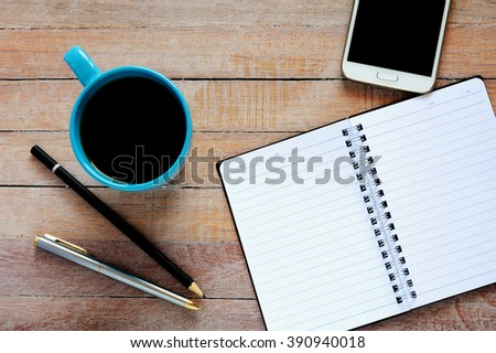 Top view on opened notebook, smartphone, pen and cup of coffee on rustic office desk. - stock photo
