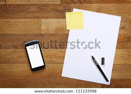 Top view on paper, pen, sticky note and smartphone on wooden office desk. - stock photo