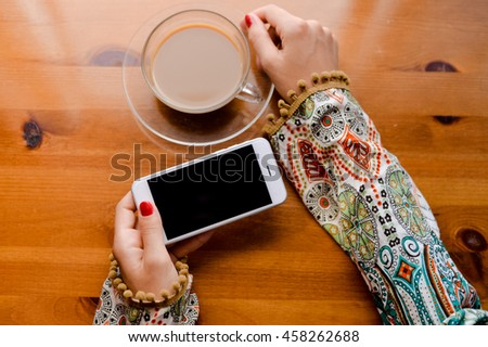 Top view on person working on mobile phone, hands and coffee cup on wooden desk background. - stock photo