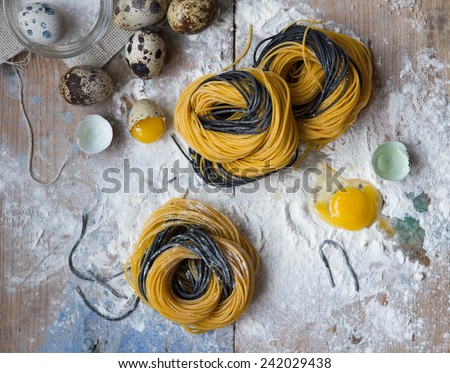 Top view on plane with raw homemade italian pasta tagliatelle with flour and speckled quail eggs, and vintage rolling pin over old wooden table. See series - stock photo