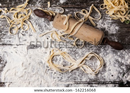Top view on raw homemade pasta with flour, vintage rolling pin and infinity symbol over old wooden table - stock photo